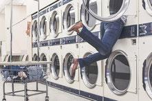 Person steckt bis zur Hüfte in einer Waschtrommel im Waschsalon