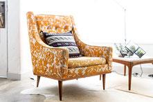 gepolsterter Sessel mit gelbem Muster, Couchtisch und Teppich