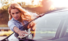 Frau wischt Windschutzscheibe von PKW ab