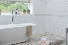 weißes Badezimmer mit Badewanne, Fenster, Pflanzen und Teddybär