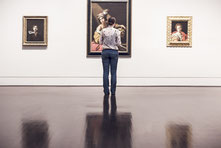 Frau in Kunstgallerie betrachtet eines von drei Gemälden