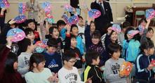 うちわを振ってマスコット決定を祝う平岸高台小の児童(3月1日北海道新聞より)