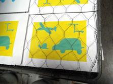 türkisene Objekte hinter Gittern auf gelbem Hintergrund - Flugzeug. Tretroller, Schnecke und Auto