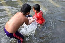 Kids schwimmen in den Klongs von Bangkok