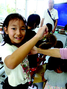 初めて見る本物のイガグリにびっくり。奥は清水さん=15日、竹富小中学校