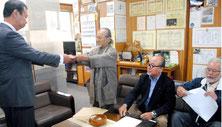 役場移転の早期実現を求める要請書を川満町長に手渡す石垣さん(左から2番目)と上勢頭さん、津嘉山さん=3日午前、町役場