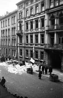 Schaulustige umringen die Trümmer vor dem 5-geschossigen Stadthaus, 2 Karren stehen bereit (Plünderung?)