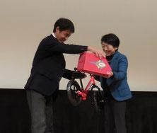 """""""聴覚障害教育支援NPO法人言葉の森くるめ""""の山﨑理事長へランニングバイクとヘルメットを寄贈"""