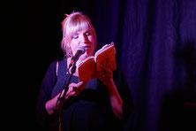 Poetry-Workshop mit Kaddi Cutz im *sowieso* in Dresden | Das Foto zeigt die blonde Kaddi am Mirkofon stehend und ein Buch in den Händen haltend bei einer Lesung.
