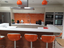 Bespoke kitchen with a large breakfast bar and orange stools designed by Brighton and Hove kitchens