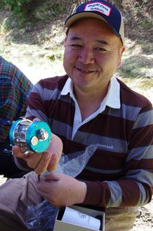 「Brightliver」の松本さんが、すごく手のかかった仕上げが施されたワンオフのベイトリールを手にニッコリ。先月末に京都の広河原で開催されたウッドスティックの会場にて。