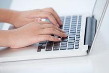 Frauenhände schreibend auf Computer-Tastatur (Laptop)