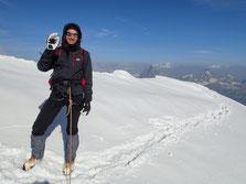 Gérard au sommet du Lyskaam ouest. Plus loin, Cervin et Dent Blanche fument