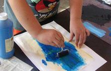 Kind rollte mini-Farbwalze mit blauer Farbe  auf weissem Papier