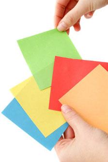 eine Hand sucht eine grüne Farbkarte aus der anderen Hand aus