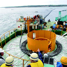 海底送水管の敷設工事が始まった。写真奥が竹富島。町議の所管事務調査も行われた=23日、竹富島沖の作業船から撮影(竹富町提供)