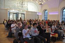 Viele Menschen sitzen im Palais Stutterheim und verfolgen die Frühjahrsvollversammlung des Stadtjugendrings.