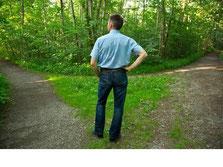 Ein Mann, vor einer Weggabelung im Wald, der sich fragt, welche Entscheidung nun die richtige für Ihn ist
