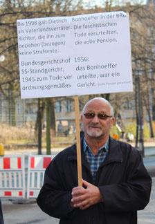 """Ein Mann mit Plakat über den Justizmord an Dietrich Bonhoeffer durch Nazi-Richter, durch ein Schandurteil des Bundesgerichtshof 1956 """"legitimiert"""". Foto: Helga Karl"""