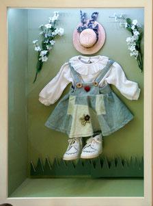 Kinderkleidung in einem Holzrahmen und ART-Glas