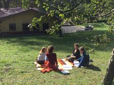 Menschen die auf einer Decke in der Natur sitzen und sich unterhalten