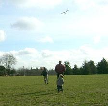 2 hommes et un enfant dans un champ, après un lancement d'un planeur radiocommandé Coquillaj Aeromod lancé par le saumon