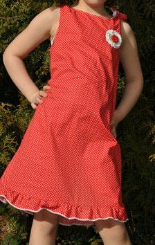 Knielanges Kleid aus Baumwolle in rot mit weißen Punkten. Auf der Brust ist eine Häkelblume.
