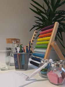 Auf dem Bild sieht man einen Arbeitsplatz mit einem Block und einem Kugelschreiber, einem Glas Wasser und einem Rechenschieber.