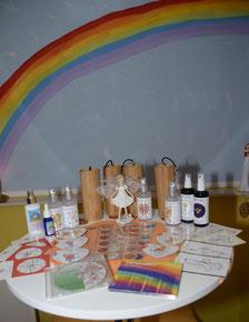 Weißer Tisch mit Koschi Klängen, Ingrid Auer Sprays, Energie Symbolen, Regenbogen und Klangwelten CD