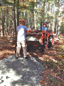 Adrian Curtis, a student with ACCESS, directing Michael Nerrie with a tractor-bucket load of gravel. They are building an accessible hiking trail to one of the vernal pools at Distant Hill Gardens.