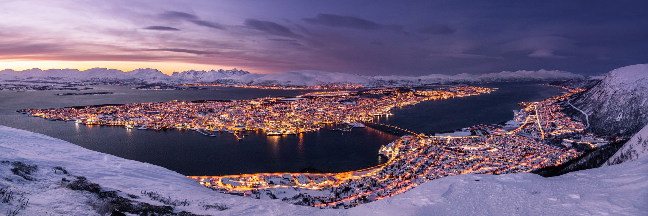 Nightscape panorama with the lights of the city of Tromso in winter.