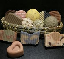 verschiedene Seifenstücke mit unterschiedlichen Inhaltsstoffen in einem genähten Graskörbchen