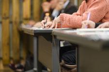 講演会でメモ取る聴講者の画像