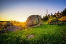 Franzosenstein mit Sonnenstrahlen und grüner Wiese in Bad Traunstein