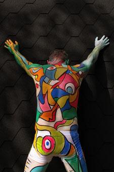 In Pop-Art-Manier bunt bemalter Mann steht mit dem Rücken und erhobenen Händen an eine Wand gestützt  vor dem Betrachter.