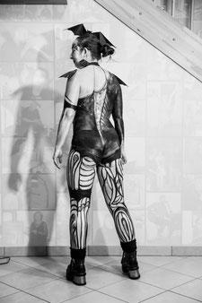 Eine Frau wurde in schwarz und silber bemalt und als Fledermaus kostümiert.