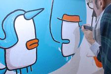 Künstler zeichnet ein Einhorn in Acryltechnik an die Wand.