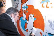 Künstler malt eine Katze in Acryltechnik an die Wand.