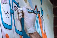 Künstler zeichnet eine Brille in Acryltechnik an die Wand.