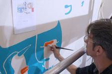 Künstler malt ein Einhorn in Acryltechnik an die Wand.