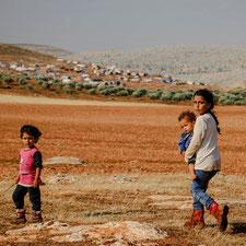 Drei Mädchen in der Wüste, im Hintergrund sind Notunterkunft für Geflüchtete