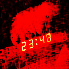 Grell leuchtende Ziffern einer Digitaluhr im Dunkeln