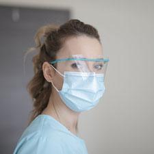 Krankenpflegerin mit Maske blickt nachdenklich in die Kamera