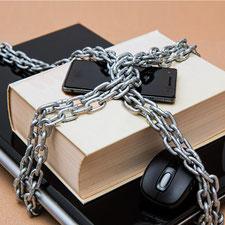 Notebook, Buch und Handy mit schwerer Eisenkette umwickelt