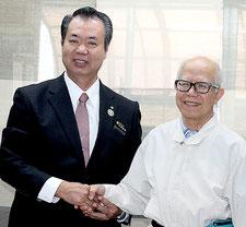 黒島診療所に久保利夫医師(右)が就任。川満町長から委嘱状が手渡された=1日午前、町長室