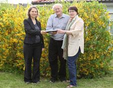 Pfarrerin Katharina Wendler, Stiftungsratsmitglied der Nussbaum Stiftung, überreicht den Scheck an Ronald Koch und Bärbel Morsch (v.l.). Foto: dyh