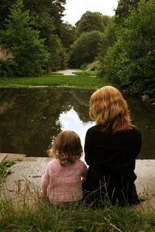 Mutter und Kind sitzen am Teich