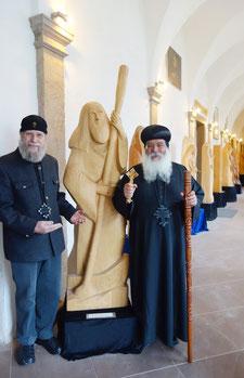 """Der Holzbildhauer und Diakon mit Bischof Damian und dem """"Fährmann"""""""