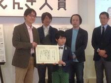 未来世代の代表、鈴木福くんから賞状を手渡される上岡理事長