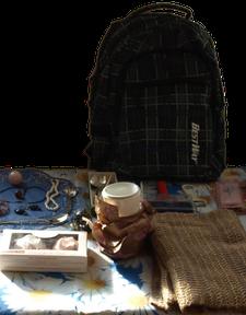 Tisch mit Keramik wie Becher und Textiliem wie Schal, Seidenstrümpfen, Rucksack